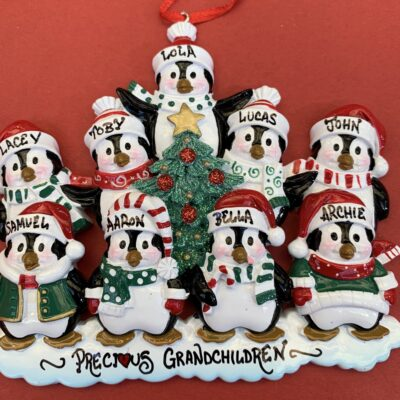 9 Penguins on a decoration surrounded by a Christmas Tree, with snow underneath the penguins feet.